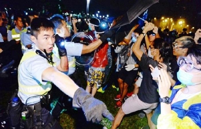 Протестующие защищаются зонтиками во время разгона в Гонконге. Фото: скриншот/ntd.tv