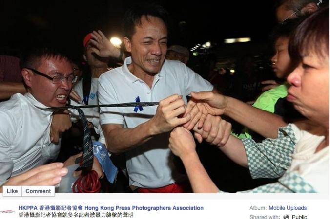 Противник демократических протестов (в центре) тянет за галстук корреспондента TVB (слева) во время проправительственного митинга в районе Цим Ша Цуй в Гонконге 25 октября 2014 года. Фото: Screenshot/Facebook of Hong Kong Press Photographers Association