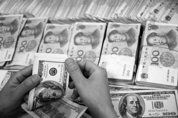 Доллары США пересчитываются на фоне пачек китайских юаней в банке города Хауйбэй, провинция Аньхой, Китай, 23 сентября 2014 года. Фото: STR/AFP/Getty Images