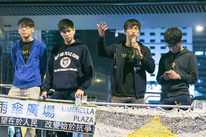 Алекс Чоу, генеральный секретарь Федерации студентов Гонконга, вместе с другими лидерами выступает перед демонстрантами после того, как ему отказали во въезде в Пекин, 15 ноября 2014 года. Фото: Benjamin Chasteen/Epoch Times