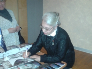 Стелла Никифорова ставит автограф на своей книге.. Фото: Татьяна Петрова/Великая Эпоха (The Epoch Times)