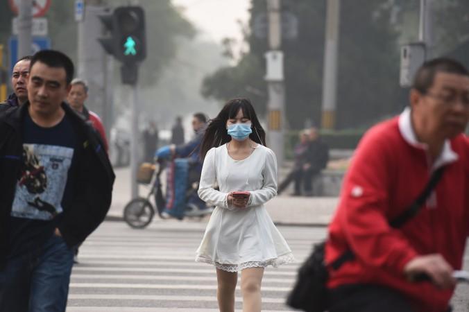 Девушка идёт в маске из-за смога в Пекине 20 октября 2014 года. Пекин возобновил нормальную жизнь после закрытия саммита АТЭС 11 ноября 2014 года. Некоторые петиционеры были освобождены, тепло подаётся, заводы заработали, с автомобилей сняты ограничения и так далее. Фото: Greg Baker/AFP/Getty Images