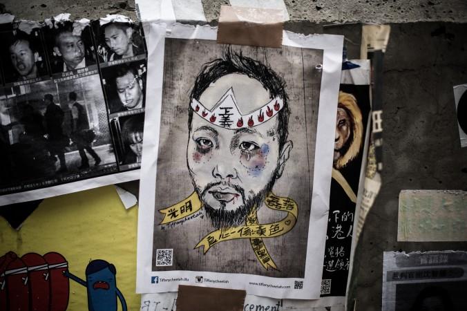 Плакат с изображением члена Гражданской партии Кена Цзана, которого избили сотрудники полиции в штатском, установлен на главном месте протестов в Адмиралтейском районе Гонконга 23 октября 2014 года. Семь полицейских, участвовавших в избиении, были задержаны 26 ноября. Фото: Philippe Lopez/AFP/Getty Images