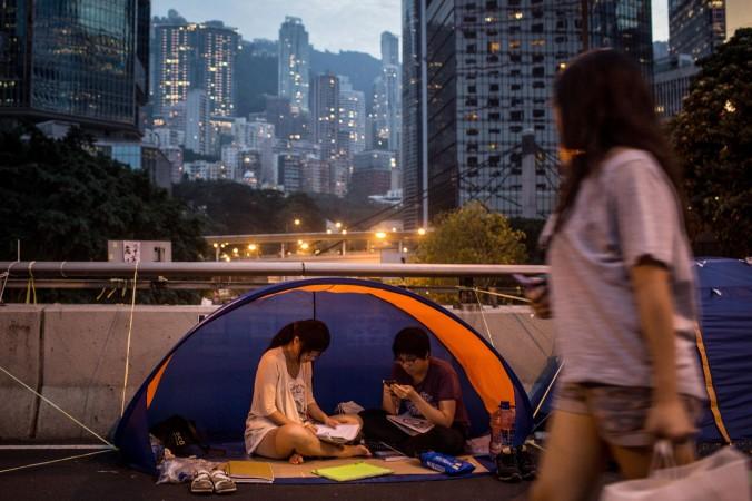 Демократические активисты читают в палатке возле правительственного комплекса в Гонконге 26 октября 2014 года. Студенту, члену Scholarism, было отказано во въезде в Шэньчжэнь, который граничит с Гонконгом, 7 ноября 2014 года. Фото: Chris McGrath/Getty Images
