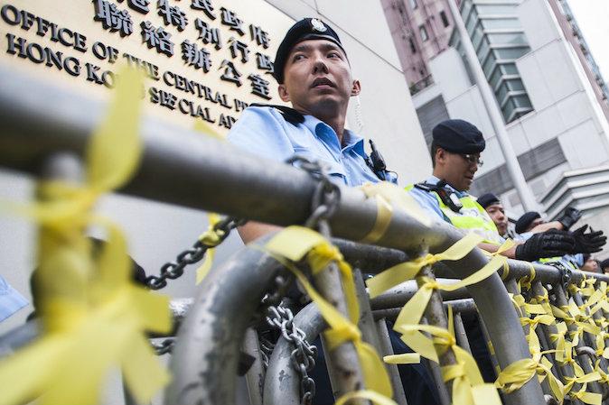 Полицейские блокируют подход к китайскому отделению по связям в Гонконге 9 ноября 2014 года. Сотни протестующих собрались у офиса, призывая к диалогу чиновников в Пекине. Фото: Xaume Olleros/AFP/Getty Images