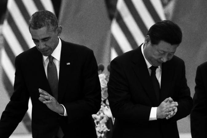 Президент США Барак Обама (слева) садится на свое место, а лидер Китая Си Цзиньпин аплодирует на обеденном  банкете в Большом зале народных собраний в Пекине 12 ноября 2014 года. Фото: Greg Baker/AFP/Getty Images