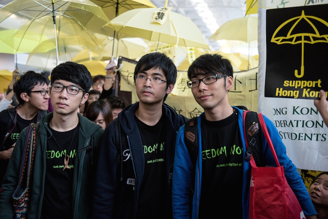 Студенческие лидеры Натан Лав (слева), Алекс Чоу и Исон Чун (справа) стоят в окружении протестующих сторонников демократии в международном аэропорту Гонконга перед их запланированным вылетом в Пекин 15 ноября 2014 года. Лидеры протестов говорят, что они отправляются в столицу, надеясь донести свои требования по проведению политических реформ центральному руководству страны. Фото: Alex Ogle/AFP/Getty Images