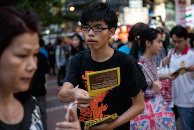 Студенческий лидер Джошуа Вон раздаёт листовки в поддержку демократических протестов в районе Causeway Bay, Гонконг, 16 ноября 2014 года. Фото: Alex Ogle/AFP/Getty Images