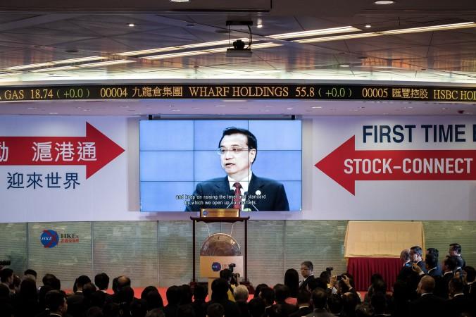 Премьер Китая Ли Кэцян показан на большом экране во время запуска слияния бирж Шанхая и Гонконга 17 ноября 2014 года, Гонконг. Ранее власти угрожали, что открытие слияния будет отложено из-за «зонтичного движения». Законодатель Синь Чхун-кай назвал это попыткой остановить «зонтичное движение». Фото: Philippe Lopez/AFP/Getty Images
