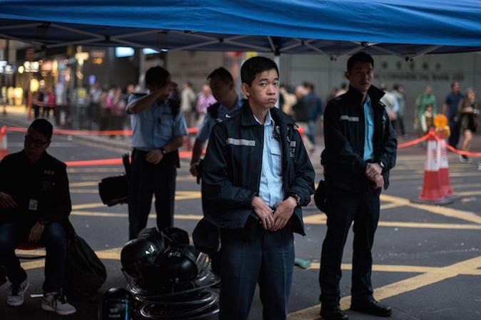 Полицейский смотрит на баррикады, возведённые демократическими протестующими в районе Монгкок, 19 ноября 2014 года, Гонконг. Фото: Alex Ogle/AFP/Getty Images