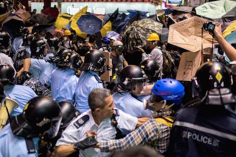 Полицейские выхватили из толпы протестующего, 25 ноября 2014 года, Монгкок. Власти Гонконга убрали баррикады на месте протеста в Монгкоке. Это было одно из наиболее ожесточённых столкновений за всё время почти 2-месячных протестов. Фото: Alex Ogle/AFP/Getty Images