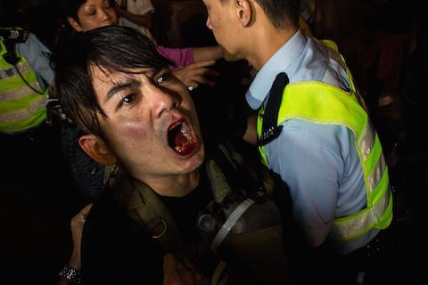 Полицейские арестовывают мужчину во время стычки с демонстрантами в Монгкоке 25 ноября 2014 года. Фото: Lam Yik Fei/Getty Images