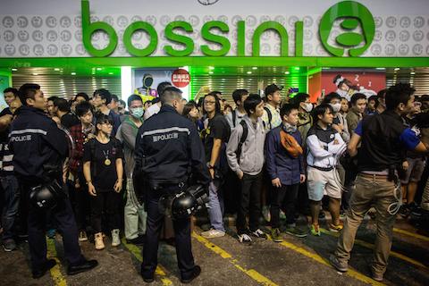 Полиция не позволяет продемократическим протестующим и пешеходам пересекать улицу в Монгкоке, 26 ноября 2014 года, Гонконг. Фото: Chris McGrath/Getty Images