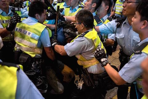 Полицейские окружают протестующих сторонников демократии в Монгкоке, 26 ноября 2014 года, Гонконг. Фото: Alex Ogle/AFP/Getty Images