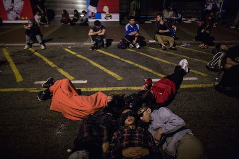 Продемократические протестующие спят на асфальте в Монгкоке 27 ноября 2014 года, Гонконге. Фото: Lam Yik Fei/Getty Images