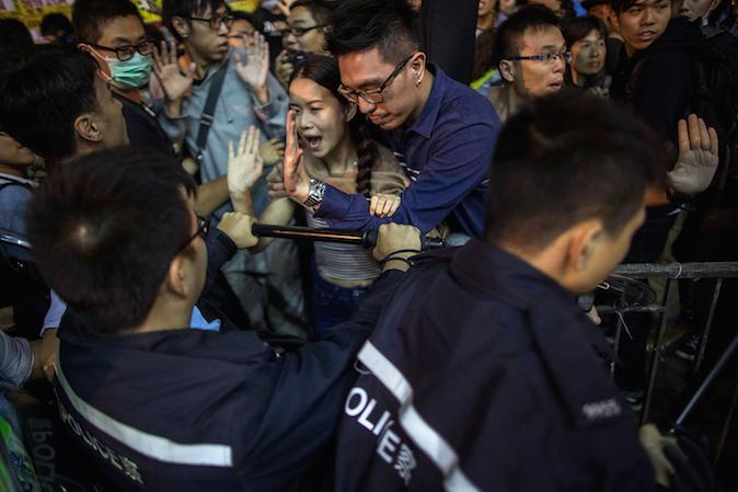 Продемократические протестующие и пешеходы спорят с полицейскими на улице в Монгкоке, 26 ноября 2014 года, Гонконге. Фото: Lam Yik Fei/Getty Images
