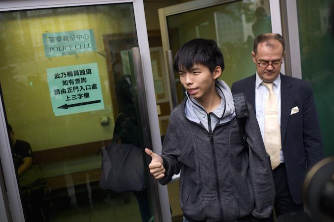 Студенческий лидер Джошуа Вон (в центре) показывает «большой палец», выходя из здания суда со своим адвокатом Майклом Видлером 27 ноября 2014 года. Фото: Aaron Tam/AFP/Getty Images