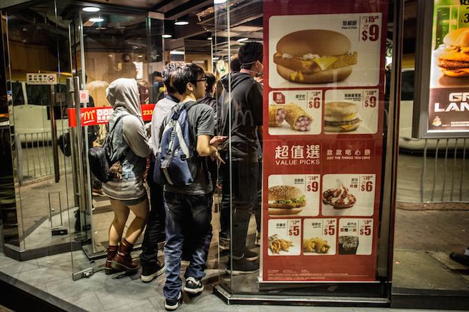 Продемократические активисты убегают от полиции в магазин McDonalds на улице в Монгкоке 29 ноября 2014 года, Гонконг. Хотя полиция зачистила места протестов, столкновения с демократическими активистами в районе Монгкок продолжаются. Фото: Chris McGrath/Getty Images