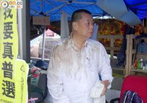 Медиамагнат Джимми Лай стоит в платке протестующих после того, как в него бросили потроха. Он сказал, что это просто запах. Фото: theepochtimes.com