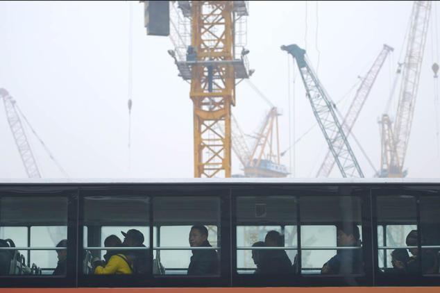 Автобус проезжает мимо стройки в Пекине 20 ноября 2014 года. Фото: WANG ZHAO/AFP/Getty Images