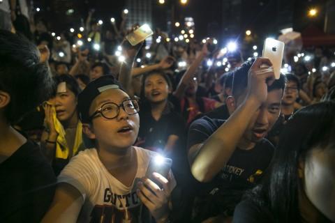 Студенты включили фонарики на мобильных телефонах во время демократических протестов в Гонконге 1 октября. СМИ сообщили, что китайский режим прослушивает разговоры гонконгцев по сотовым телефонам из соседней горной военной базы. Фото: Paula Bronstein/Getty Images
