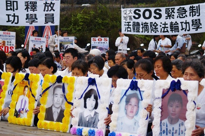 Сторонники Фалуньгун держат портреты своих единомышленников, погибших в Китае в результате преследования, а также плакаты с призывами к мировому сообществу помочь остановить репрессии. Город Гаосюн, Тайвань. Фото: ЦАН