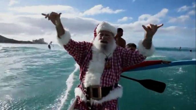 Санта-Клаус в полном обмундировании рассекает волны на каноэ и распевает гавайскую рождественскую песню. Скриншот видео.