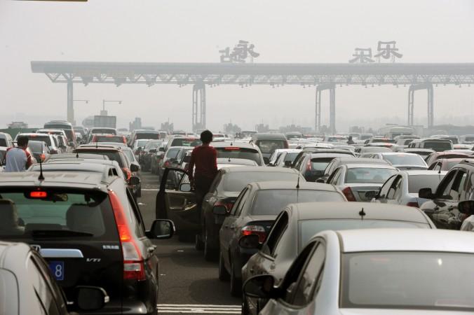 Водители вышли из автомобилей, чтобы рассмотреть пробку перед въездом на платный участок дороги, окраина Пекина, 2 октября 2010 года. По некоторым оценкам, в 2014 году китайские водители заплатили 400 млрд юаней за пользование платными дорогами. Многие сомневаются в законности таких сборов. Фото: STR/AFP/Getty Images