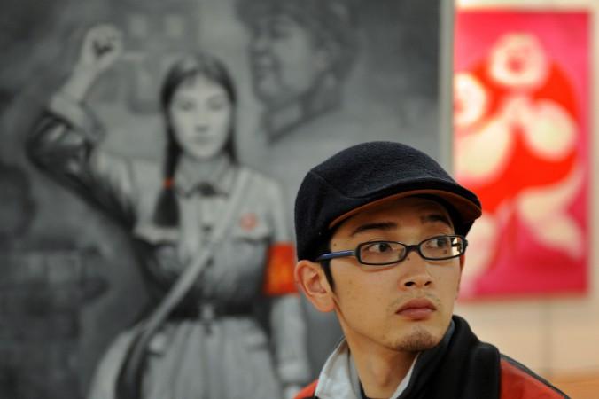 Китаец проходит мимо плаката периода «культурной революции» на художественной выставке в Шанхае 17 апреля 2008 года. Власти Китае заявили, что отправят творческих работников в сельские районы, чтобы они приобрели «правильную точку зрения». Фото: Mark Ralston/AFP/Getty Images