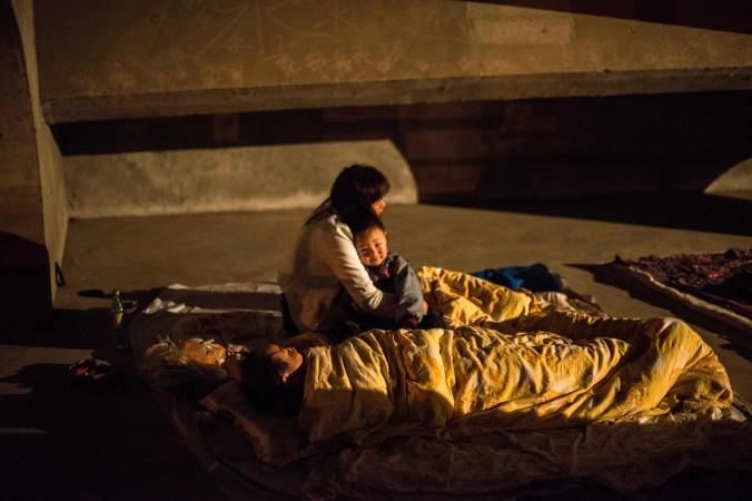 Мать обнимает своего ребёнка во временном приюте в городе Яане провинции Сычуань после землетрясения 21 апреля 2013 года. Чжан Юнлин и её 10-месячного сына в течение пяти дней незаконно удерживали сотрудники управления по планированию семьи города Линьси провинции Шаньдун. Фото: STR/AFP/Getty Images