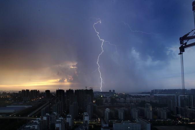 Удар молнии на закате в Ухане, столице центральной китайской провинции Хубэй, 11 августа 2013 года. Проверки в секторе недвижимости стали важной частью антикоррупционной кампании Си Цзиньпина против фракции Цзяна. Фото: STR/AFP/Getty Images