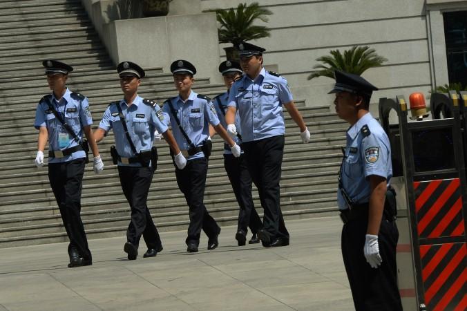 Китайские полицейские маршируют у здания суда в провинции Шаньдун, Китай. 20 декабря 2014 года в южной китайской провинции Гуандун полицейские вытолкали адвоката Лю Чжэнцина из суда, когда он попытался защищать своего клиента, последователя Фалуньгун. Фото: Mark Ralston/AFP/Getty Images