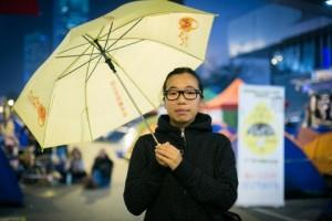 Попо Лай держит зонтик, символ продемократических протестов, в конце ноября 2014 года. Она и многие другие студенты стараются убедить общественность в преимуществах демократии в Гонконге. Фото: Benjamin Chasteen/Epoch Times