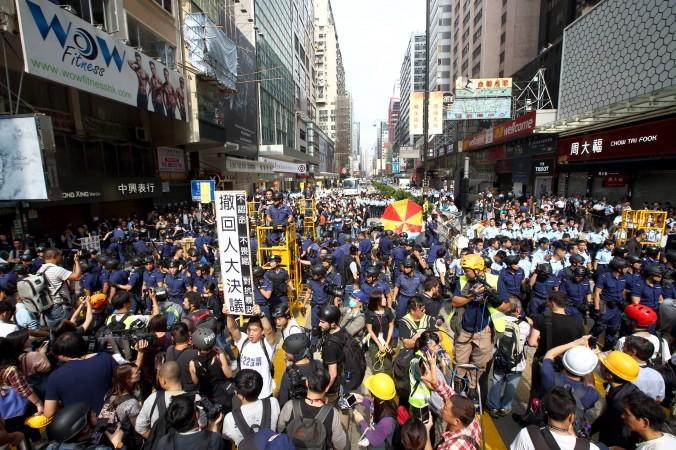 Протестующий в белой футболке держит плакат с требованием, чтобы ПК ВСНП отозвал своё решение, ограничивающее всеобщее избирательное право в Гонконге, 26 ноября 2014 года, Монгкок. Фото: CS Poon/Epoch Times