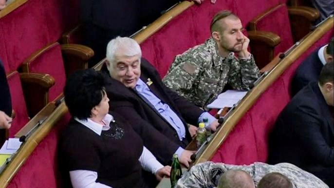Рядом с респектабельными политиками Михаил Гаврилюк в своем камуфляже никак не выглядит депутатом. Скриншот видео.