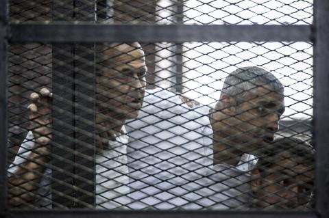 Журналисты «Аль-Джазиры» — австралиец Петер Гресте (слева) и его коллеги, египтяне Мохаммед Фадель Фахми (в центре) и Бахер Мохаммед — слушают вердикт египетского суда 23 июня 2014 г. Они были обвинены в сотрудничестве с организацией «Братья-мусульмане» и приговорены к срокам от 7 до 10 лет. Фото: Khaled Desouki/AFP/Getty Images