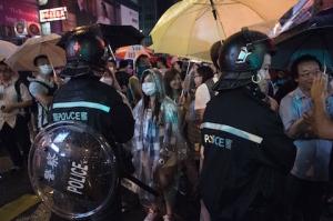 Протестующие стоят под дождём рядом с полицейскими в Монгкоке, Гонконг, 22 октября 2014 года. Фото: Nicolas Asfouri/AFP/Getty Images