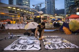 Художник Брайан Чуй рисует протестующую девушку в главном лагере студентов в Адмиралтействе 24 октября 2014 года, Гонконг. Фото: Paula Bronstein/Getty Images
