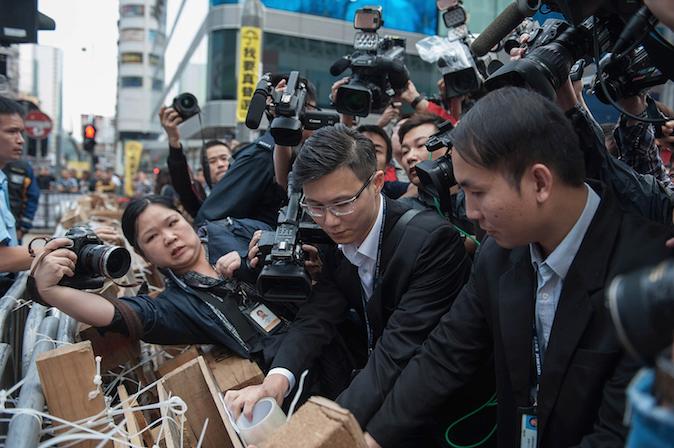 Судебные приставы доставили копию судебного запрета на протесты на Argyle Street в Монгкоке, Гонконг, 19 ноября 2014 года. Запрета добивалась автобусная  компания Chiu Luen Public Light Bus Company Чиу Luen, которая сообщила о решении суда в местных газетах. Фото: Anthony Kwan/Getty Images