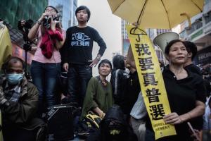 Представитель Гражданской партии законодатель Клаудия Мо (в центре) стоит с протестующими на самодельной сцене в то время, когда судебные приставы удаляли палатки студентов в Монгкоке 25 ноября 2014 года. Фото: Philippe Lopez/AFP/Getty Images