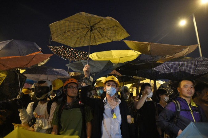Демонстранты держат зонтики, символ продемократических протестов, во время столкновения с полицией у здания правительства в Гонконге 30 ноября 2014 года. Протестующие добиваются свободных выборов главы Гонконга в 2017 году. Фото: Philippe Lopez/AFP/Getty Images
