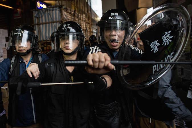 Гонконгский полицейский делает угрожающий жест. Фото: Chris McGrath/Getty Images