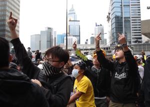 Протестующие показывают полицейским непристойный жест. Фото: Dale de la Rey/AFP/Getty Images