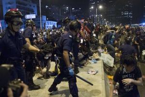 Полицейские разгоняют протестующих возле здания правительства в Адмиралтейском районе Гонконга на рассвете 1 декабря 2014 года. Фото: Dale de la Rey/AFP/Getty Images