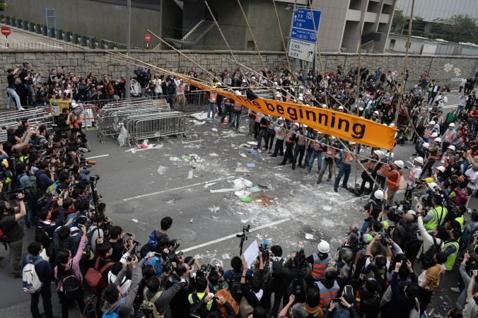 Представители СМИ и зеваки наблюдают, как рабочие убирают баррикады, построенные демократическими протестующими в основном своём лагере в Адмиралтейском районе Гонконга 11 декабря 2014 года. Фото: Dale de la Rey/AFP/Getty Images