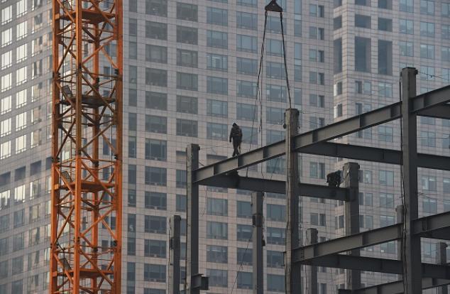 Строители ходят по стальным балкам строящегося здания в Пекине 18 декабря 2014 года. Фото: GREG BAKER/AFP/Getty Images
