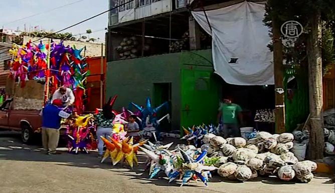 Рождественскую пиньяту привязывают к горизонтально натянутой верёвке или вешают на крюк и стараются разбить её палкой. Скриншот видео.