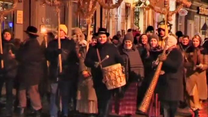 Толпа ряженых, пыхтя и отдуваясь, тащит по улицам Риги тяжеленное бревно. Скриншот видео.