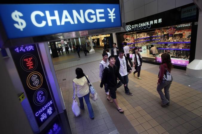 Люди проходят мимо обменника валюты в гонконгском районе Козуэй-Бей 28 апреля 2010 года. Фото: Ed Jones/AFP/Getty Images