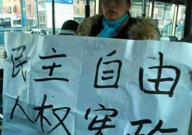 Правозащитница Ван Фан из провинции Хубэй держит в автобусе плакат: «Демократия, свобода, права человека, конституция». 4 декабря 2014 года, в «День Конституции» КНР, её арестовала полиция. Фото: NTD